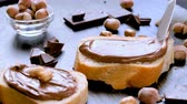 Spreading hazelnut chocolate cream on bread closeup. Delicious breakfast concept. Stok Video