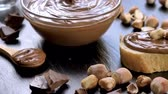 Chocolate spread in glass bowl with hazelnuts on black table. Serving a delicious breakfast concept. Dolly shot.