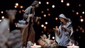 salvador : Christmas manger nativity scene with figures and atmospheric candles lights. Dolly shot in 4k.