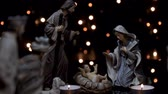 Christmas manger nativity scene with figures and atmospheric candles lights. Dolly shot in 4k.