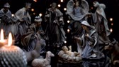Christmas manger nativity scene with figures and atmospheric candles lights. Focus moves from candles to Joseph father and then to Jesus baby. 4k