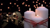Christmas gift and candles with red ribbon burning in atmospheric light. 4k Wideo