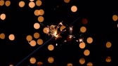 Sparkler burning in front of ambient lights. Gun powder sparks shot against bokeh lights background. 4k Stok Video