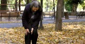 doloroso : Senior woman walking in autumn park and having knee pain. Arthritis pain concept. The person comes in focus. Stock Footage