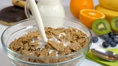 flocos de milho : Pouring milk on cereals flakes for healthy and organic breakfast. Slow motion shot. Vídeos