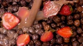 nutricional : Milk with chocolate flowing on cocoa cereals with strawberries. Healthy eating for breakfast concept. Slow motion footage.