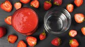 nutricional : Fresh strawberry smoothie flowing in glasses ready to drink. Healthy drinking concept. 4k Stock Footage