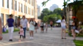 нечеткий : People walking walk down the street at a festival in the city on a sunny day. Background blur.