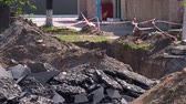 kırmızımsı : Pieces of broken asphalt and a dug pit with a protective red-white ribbon at the construction site. Replacement of pipes for heating of a heating main near an apartment house Stok Video