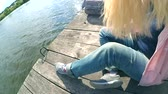 suíça : Blond girl in blue jeans sits on the edge of an old wooden pier berth dock near the lake pond with inclined head close-up on sunny day. Rest relax on the nature near the water. Concept