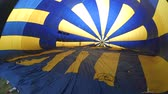 dobrado : Inflation of a large balloon aerostat that lies on the ground. Preparation of a flight air balloon for flight. Inside view close-up. Balloon or aerostat yellow blue inflated with air by a fan blower
