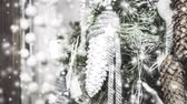 cone : Decorative white Christmas New Years toy pine cone hanging on Christmas tree close-up. Snowfall, falling snowflakes, spots white color. Winter Christmas New Year background. Cinemagraph seamless loop