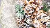 pinha : Natural Christmas New Years toy pine cone and Christmas tree branch close-up. Snowfall, falling snowflakes, spots white color. Winter Christmas New Year background. Cinemagraph seamless loop