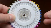 портниха : A seamstress woman pulls out a pin with plastic head from a set of white discs. Dressmaker get a multi-colored needle and put it back Стоковые видеозаписи