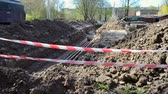 jeskyně : Large pit dug in the ground for the purpose of order remot and for laying water pipes of city communications fenced with a protective red tape, on construction site