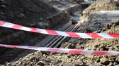 označení : Large pit dug in the ground for the purpose of order remot and for laying water pipes of city communications fenced with a protective red tape, on construction site