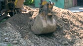 dredging : Tractor pits the ground. Backhoe piles up the ground close-up. Old tractor in maintenance work. Technical city works. Repair urban work close-up. Excavator covered with earth pit at day. Stock Footage