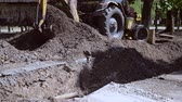 pala : Tractor pits the ground. Backhoe piles up the ground close-up. Old tractor in maintenance work. Technical city works. Repair urban work close-up. Excavator covered with earth pit at day. Archivo de Video