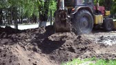 dipper : Tractor pits the ground. Backhoe piles up the ground close-up. Old tractor in maintenance work. Technical city works. Repair urban work close-up. Excavator covered with earth pit at day. Stock Footage