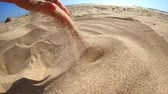 deslizamento : Slow motion. Low angle. Girl picks up handful of sand in her palm and sprinkles or pours it closeup. The girl scoops up sand and spills it. Womans hand scatters sand through his fingers. Stock Footage