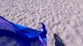 Transparent shawl in wind over sand of sea shore with dark shadow. Abstract conceptual background. Scarf cloth fluttering in wind over sand. Wave purple pink cloth satin fabric background. Slow motion