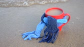 Red mug with coffee tied with blue knitted scarf stands on sandy beach of ocean sea waves. Concept warm mood travels relax ocean sea vacation holiday rest Stok Video