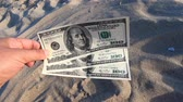 Girl holding money bill of 300 dollars on background of over sand of sea ocean sandy beach close-up. Hand wave sea ocean money dollars vacation. Concept finance money holiday traveling Stok Video
