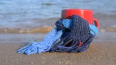 dinlenmek : Red mug with coffee tied with blue knitted scarf stands on sandy beach of ocean sea waves. Concept warm mood travels relax ocean sea vacation holiday rest Stok Video