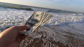 monetário : Man holds three hundred dollar banknotes in his hands on a background of the sea and white foam with waves and blue sky close-up. Banknotes move due to strong wind. Slow motion
