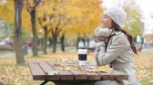 mixed race : Fall woman sitting in autumn park with colorful yellow leaves falling from trees. Smiling happy mixed race Asian Caucasian young female professional enjoying outdoor lifestyle Stock Footage