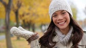 örgü : Fall woman portrait in autumn showing presenting open hand with copy space on fall foliage background in city park. Beautiful young multiracial woman walking in autumn in city forest park in trench coat. Stok Video