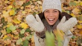 setembro : Fall woman excited and happy with autumn leaves falling. Cheerful and joyful smiling girl enjoying fall foliage with a smile. Beautiful young mixed race Asian Caucasian female model
