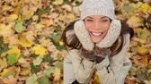 seasonal : Autumn woman in yellow leaves portrait. Fall portrait of happy lovely and beautiful mixed race Asian Caucasian young woman looking at camera and to side in forest in fall colors foliage.