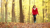 setembro : Fall woman happy running in autumn forest happy having fun laughing in beautiful colorful forest foliage outdoors. Joyful playful girl in red coat in yellow forest. Mixed race Asian Caucasian female model outside.