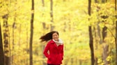 caminhada : Autumn woman happy running in fall forest having fun laughing in beautiful colorful forest foliage outdoors. Joyful playful girl in red coat in yellow forest. Mixed race Asian Caucasian female model outside.