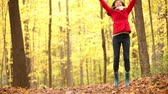 setembro : Fall woman happy throwing autumn leaves having fun laughing in beautiful colorful forest foliage outdoors. Joyful playful girl in red coat in yellow forest. Mixed race Asian Caucasian female model outside.