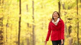 ходить : Autumn woman happy throwing fall leaves having fun laughing, playing and running in beautiful colorful forest foliage outdoors. Joyful playful girl in red coat in yellow forest. Mixed race Asian Caucasian female model outside. Стоковые видеозаписи