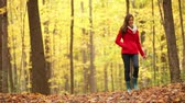mulheres : Autumn woman happy walking in fall forest looking around having fun smiling in beautiful colorful forest foliage. Girl in red coat in yellow forest. Mixed race Asian Caucasian female model outside.