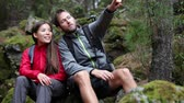 dva lidé : Hiking couple. Young people hikers having fun outdoors in forest.Multiracial couple, Asian woman, Caucasian man. From La Caldera, Aguamansa, La Orotava, Tenerife, The Canary Islands, Spain. Dostupné videozáznamy