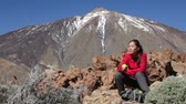 mixed race : Hiking woman eating apple after hike on Teide, Tenerife. Female trekking trough landscape scene smiling happy wearing backpack. Beautiful mixed race Asian Caucasian young woman on Tenerife, Canary Islands, Spain