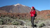 desafio : Hiker woman hiking and looking at nature on Teide, Tenerife. Female on hike stops up looking around to side enjoying scenery, then continues trekking. Beautiful multiracial Asian Caucasian model. Stock Footage