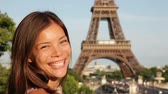 bonito : Eiffel Tower tourist woman in Paris smiling in sun enjoying tourism travel looking at Eiffel Tower in the sun on beautiful sunny summer day. Asian Caucasian mixed race female model. Stock Footage