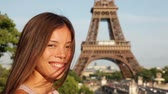 fundo : Tourist at Eiffel Tower, Paris smiling happy. Woman looking at camera smiling while on travel in France and Europe. Tourism concept with beautiful mixed race Asian Caucasian female model.