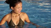 rega : Pool woman in bikini enjoying water swimming and looking around. Beautiful young female model at travel vacation enjoying sun taking a swim at resort pool. Beautiful young multiracial Asian Caucasian.
