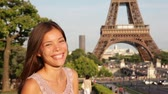 mixed race : Travel Paris woman waving hello with hand by Eiffel Tower. Happy tourist woman traveling in France, Europe. Travel concept with beautiful young multiracial Asian Caucasian female model.