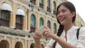 turístico : Woman tourist taking pictures in Macau, China in Senado Square or Senate Square. Asian girl tourist using smart phone camera to take photo while traveling in Macau. Travel and tourism concept.