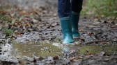 criança : Rain boots walking in mud puddle and dirt in fall. Blue woman rain boot in autumn  fall forest on rainy day.