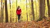 setembro : Fall woman happy walking in autumn forest forest looking around having fun smiling in beautiful colorful forest foliage. Girl in red coat in yellow forest. Mixed race Asian Caucasian female model outside.
