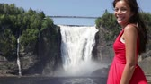 mixed race : Chute montmorency falls quebec and woman tourist smiling happy in red summer dress looking at Stock Footage