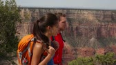 gezi : Hiking couple in Grand Canyon walking on south rim hike path. Hikers walking happy along edge with backpacks. Multi-ethnic couple, Asian woman, Caucasian man on travel holidays in Arizona, USA. Stok Video